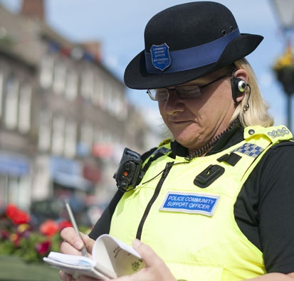 Image of Female Community Support Officer writing notes in notebook while on patrol on high street