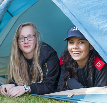 Image of two young female police cadets in tent with tent door open